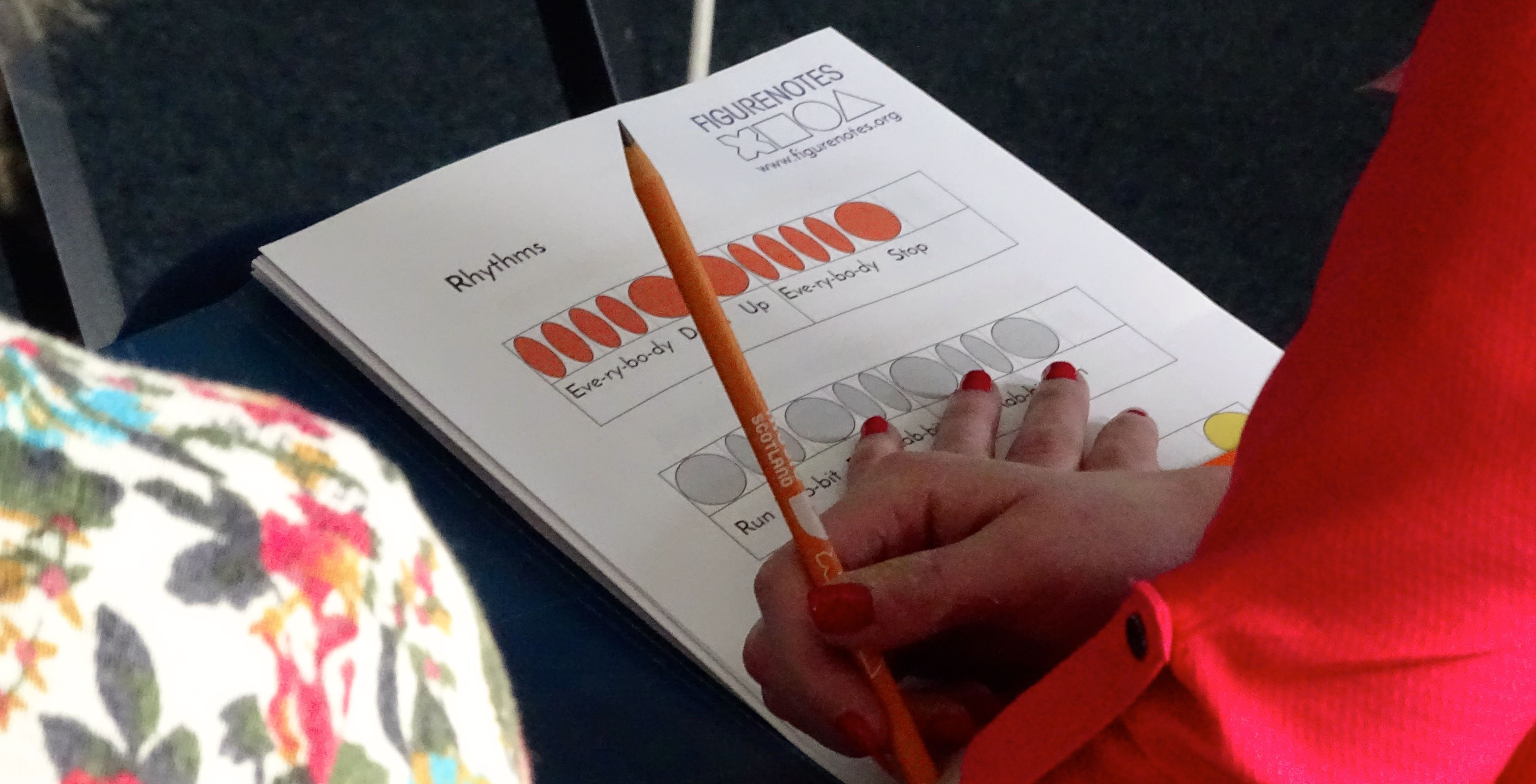 Paper resource with Figurenotes rhythms with a hand placed on top